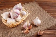 Knoflook horizontale banner Eco de landbouwconcept Gehele garlics en kruidnagels in stromand op stuk van het ontslaan op bruine h Royalty-vrije Stock Foto