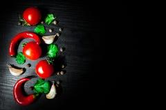 Knoflook, rode Spaanse peperpeper, tomaat op donkere houten achtergrond met exemplaarruimte Stock Afbeeldingen