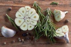 Knoflook, rozemarijn en peper op houten raad Royalty-vrije Stock Foto