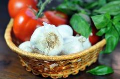 Knoflook, tomaten en basilic in whikerkom Royalty-vrije Stock Afbeeldingen