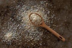 Knoflookzout van een houten lepel wordt gemorst die Stock Afbeeldingen