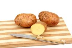 Knollen der rohen Kartoffel, die auf einem Ausschnittvorstand liegen Lizenzfreie Stockfotografie