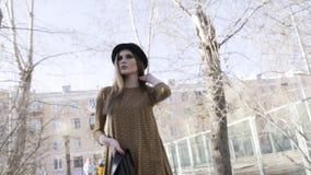 Knoopmening van de modieuze mooie vrouw wat betreft haar haar en lopen openlucht in zwart leerjasje en een hoed binnen stock videobeelden
