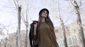 Knoopmening van het modieuze mooie vrouw lopen openlucht in zwart leerjasje en een hoed in de herfst actie Model meisje stock videobeelden
