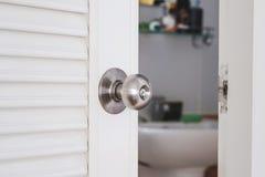 Knop van de close-up de roestvrije deur, met lichtjes open deur Stock Foto