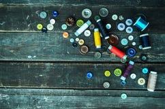 Knopen en naaiende spoelen op planken Stock Afbeelding