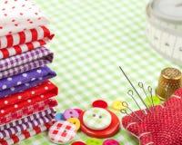 Knopen, kleurrijke stoffen, die band, speldkussen en vingerhoedje meten Stock Fotografie