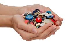 Knopen in vrouwelijke handen Stock Fotografie
