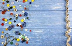 Knopfscheren und Zentimeterband auf einem blauen Hintergrund Dressmaking lizenzfreies stockbild