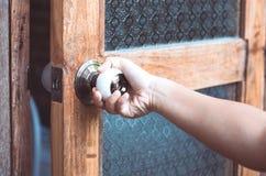 Knopp för dörr för för kvinnahandöppning/bokslut arkivfoto