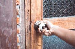 Knopp för dörr för för kvinnahandöppning/bokslut royaltyfria bilder