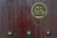 Knopp för dörr för prydnad för guld- lejon för tappning kinesisk på den röda porten royaltyfri bild