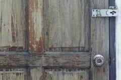 Knopp- och dörrgångjärn på gammal trädörr fotografering för bildbyråer