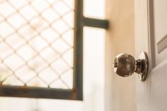 Knopp på öppen vit dörr royaltyfri foto