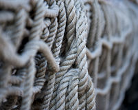 Knorrig: Aufgerolltes Seil auf Schiff Stockfotografie