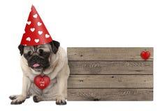 Knorrig pug van de Valentijnskaarten` s dag hondpuppy met de zitting van de partijhoed neer naast houten teken royalty-vrije stock foto's