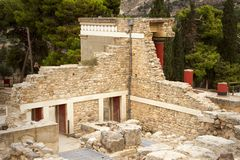 Knossos. Ruins of an ancient Minoan palace, stone walls and red columns. Crete, Greece. royalty free stock photography