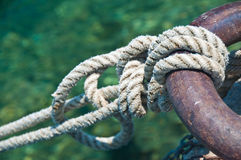 Knot. On a metallic ring holding the boat in the harbor - green background Stock Image