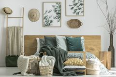 Knot cushion in basket. White handmade knot cushion in wicker basket standing by the bed with floral bedding in bright room with hats on the wall royalty free stock photo
