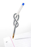 Knot Pen. Conceptual image of a pen with a knot over a black sheet of paper Stock Photo