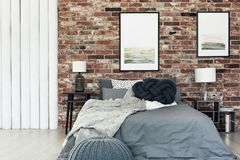 Knot pillow on bed. Dark knot pillow placed on a bed with grey bedding in stylish bedroom with posters hanging on brick wall Stock Images