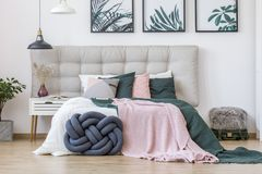 Knot pillow in cozy bedroom. Knot pillow and green and pink bedding on bed in cozy bedroom interior with lamps, posters and suitcase stock images