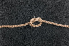 Knot of the rope lies on the natural leather Royalty Free Stock Photo