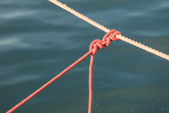 Knot on rope line over sea ocean water. Stock Image