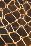 Knot rope netting orange safety net on ship metal background Royalty Free Stock Images