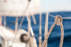 Knot on rope and sailboat crop Royalty Free Stock Images