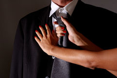 Knot a tie. Woman with red nails knoting man tie royalty free stock photos