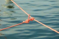 Knoten auf Seillinie über Seeozeanwasser Stockbild