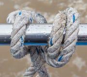 Knoten Sie das Seil, das um Stahlhalter auf Boot oder Yacht gebunden wird Stockfoto