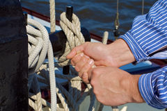 Knots. Ship´s boy knotting a rope on a boat Royalty Free Stock Photography