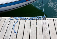Knots in a Boat Rope. A blue and white rope with several knots in it lays on a bleached out wooden dock holding a boat in place Royalty Free Stock Images