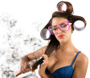 Knots at the hair. Girl with curlers combing hair with fatigue stock photos