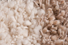Knotted carpet, detail. Knotted natural white and tan woolen carpet, close up Royalty Free Stock Images