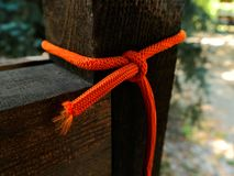 Knotted orange rope around wood stock photos