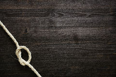 Knotted rope on dark wood Royalty Free Stock Photo