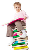 Know-all. A little girl with a book sitting on a heap of books Stock Photography