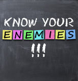 Know your enemies text on a blackboard with chalk and stickers Stock Image