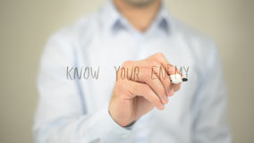 Know Your Enemy , man writing on transparent screen royalty free stock photo