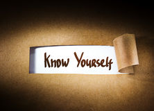 Know yourself  appearing behind torn paper Royalty Free Stock Photos