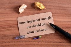 Knowing in not enough. We should do what we know text write in card on wood royalty free stock photo