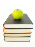 Knowledge. Green apple resting on top of a pile of books Stock Images