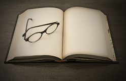 Knowledge?. Glasses on open book blank Stock Photo