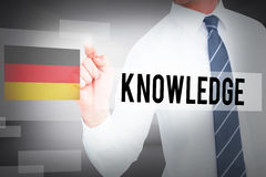 Knowledge against abstract white room. The word knowledge and businessman pointing with his finger against abstract white room Stock Photo