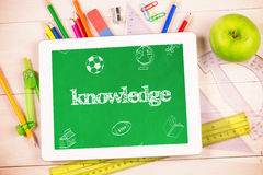 Knowledge against students desk with tablet pc Stock Photos