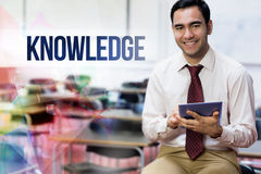 Knowledge against teacher with tablet pc in the class room Royalty Free Stock Photos