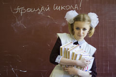 Knowledge a beret with itself. School-leaver stays near the blackboard with pile of books stock photo